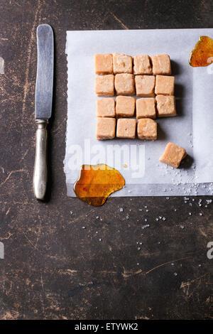 Bonbons au caramel Fudge et sur du papier sulfurisé, servi avec vintage couteau sur fond sombre. Vue d'en haut Banque D'Images