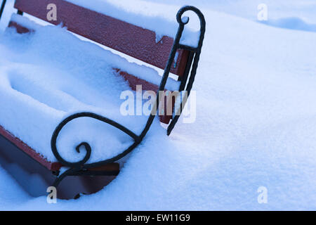 Gelé et recouvert de neige banc dans un parc local. Neige fraîche et personne autour de Banque D'Images