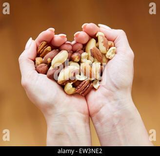 Femme tenant une poignée de noix mélangées Banque D'Images