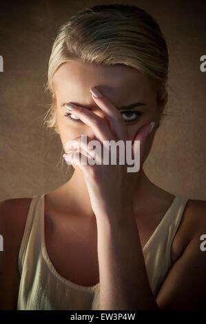 Jeune femme se cachant le visage avec la main Banque D'Images