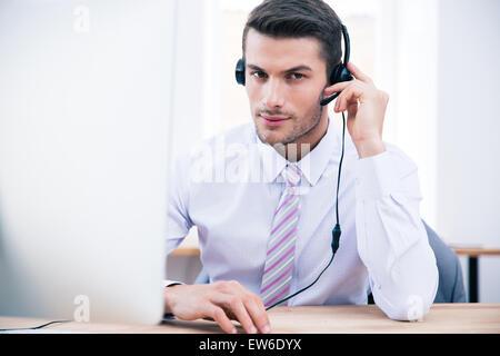 Certain homme conducteur assis sur son lieu de travail à Office et looking at camera