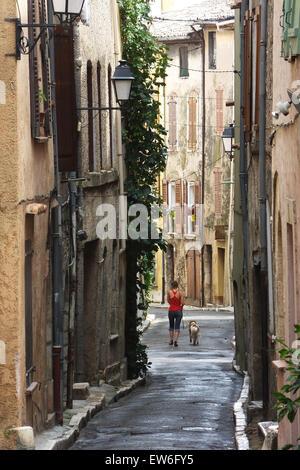 Jeune femme chien marche à travers les rues médiévales d'Aups en Provence France Banque D'Images