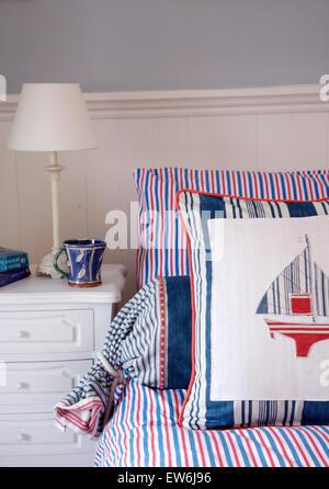 Lampe blanc peint sur la table à côté de lit avec red, white and blue bar d'oreillers et un coussin à thème nautique Banque D'Images