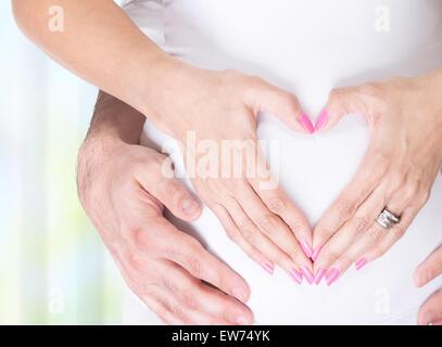 Photo gros plan de la femme enceinte et son mari se tenant la main sur le ventre en forme de coeur, de bonheur et Banque D'Images