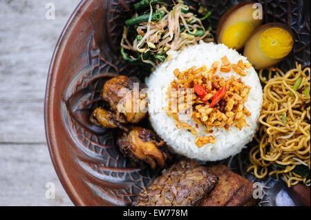 Nasi campur indonésien avec du poulet frit, des nouilles, des œufs, le tempeh et les légumes. Banque D'Images