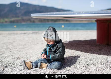 Petit garçon assis sur la plage sur un lac Banque D'Images