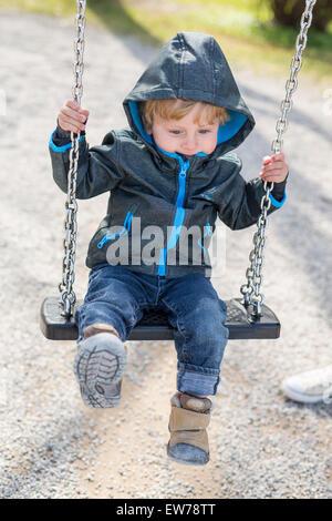 Petit garçon avec un capuchon sur une balançoire Banque D'Images