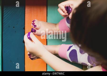 Portrait d'une jeune fille peinture salissent ses orteils Banque D'Images