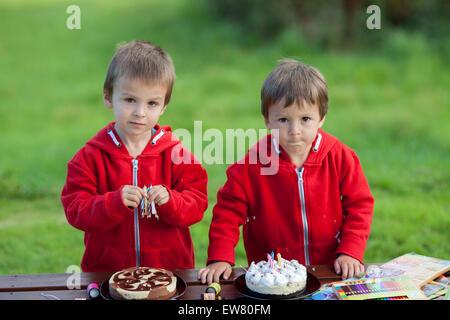 Deux adorables garçons avec des gâteaux, de plein air, fête anniversaire, s'amuser Banque D'Images