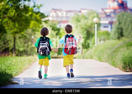 Deux adorables garçons dans des vêtements colorés et sacs à dos, à pied, de la détention et la consommation de crème Banque D'Images