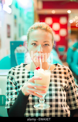Woman drinking milk shake au diner. Banque D'Images