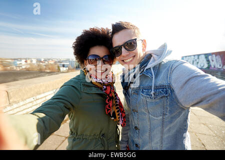 Teenage couple on city street selfies Banque D'Images