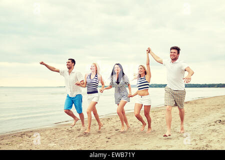 Smiling friends in running on beach Banque D'Images