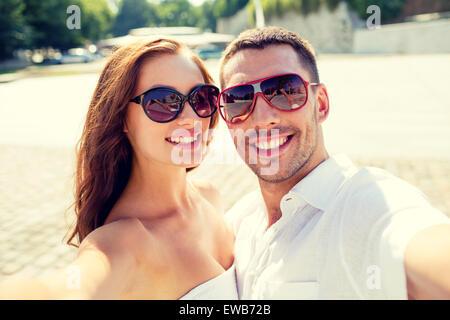 Smiling couple wearing sunglasses décisions selfies Banque D'Images