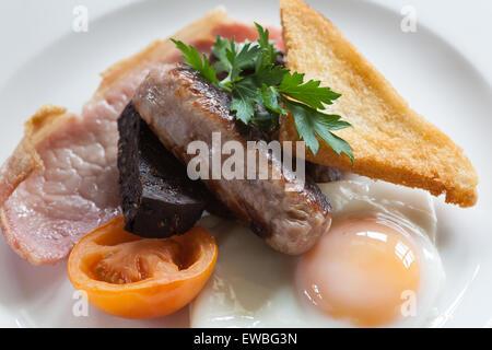 Le petit déjeuner anglais complet avec des saucisses, tomates et bacon Banque D'Images