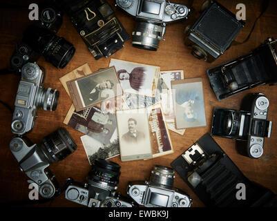Old vintage retro caméras film et photos en noir et blanc sur la vieille table en bois, des photos, des souvenirs Banque D'Images