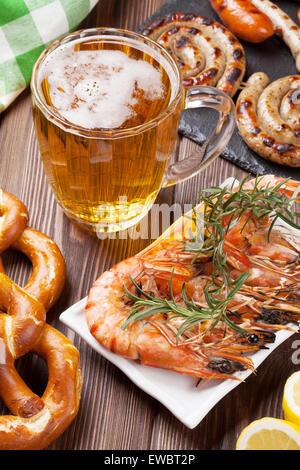 Beer mug, crevettes grillées, saucisses et bretzels sur table en bois Banque D'Images