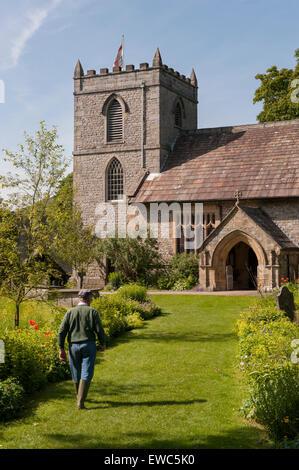 Eglise St Mary, Kettlewell, Yorkshire, Angleterre, Royaume-Uni. Avis de jardinier sur chemin dans beau jardin avec prairie, fleurs, été, ciel bleu et soleil.