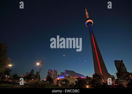 La Tour CN de Toronto et le Centre Rogers de nuit. Croissant de lune croissante, Vénus et Jupiter formant une conjonction Banque D'Images