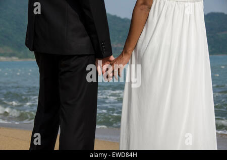 Amoureux couple walking on beach holding hands photo de mariage hugging laughing couple interracial Banque D'Images
