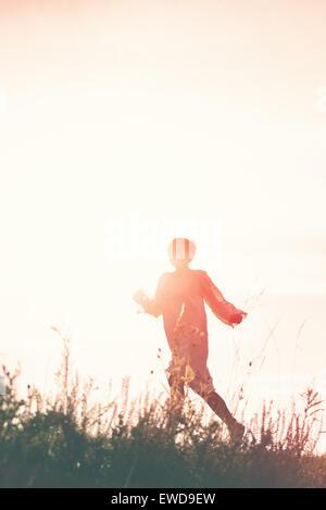 Woman Running à la liberté dans la campagne Champ, Silhouette de femme, double exposition, Vintage Retro ton effet. Banque D'Images
