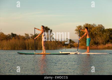 Un jeune couple bénéficiant d'une session SUP sur un après-midi d'été sur un petit lac dans le Nord de la Californie. Banque D'Images