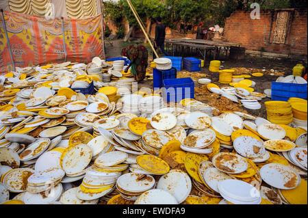 Des piles de vaisselle sale lors d'un festival à l'Uttar Pradesh, Inde. Banque D'Images