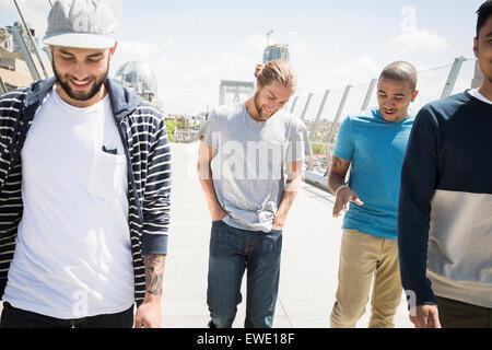 Groupe de jeunes hommes marchant le long de la passerelle Banque D'Images