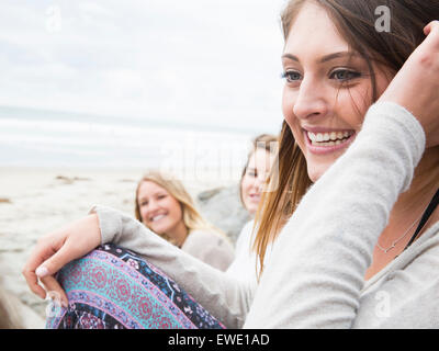 Trois jeunes femmes souriant assis sur une plage Banque D'Images