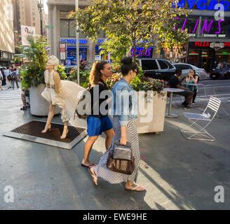 Les gens passent par l'artiste Marilyn Forever Steward Johnson sur les esplanades piétonnes dans le Broadway Garment Banque D'Images
