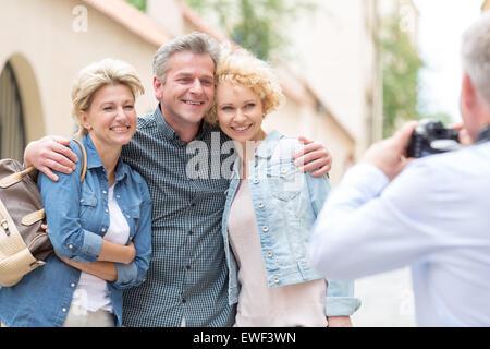 Vue arrière de l'homme photographie amis masculins et féminins dans la ville Banque D'Images