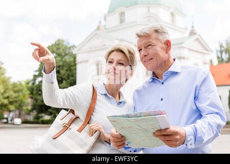 Femme d'âge moyen montrant quelque chose à l'homme tenant la carte à l'extérieur
