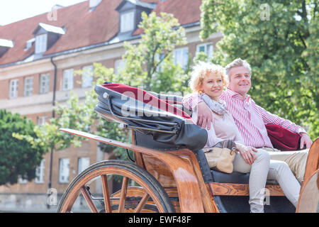 Happy middle-aged couple sitting in horse cart on city street Banque D'Images