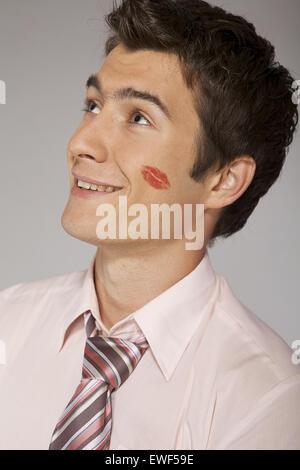 Young caucasian businessman with lipstick kiss marque sur sa joue Banque D'Images