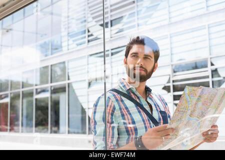 L'homme réfléchi à la voiture tout en maintenant carte routière contre la paroi en verre