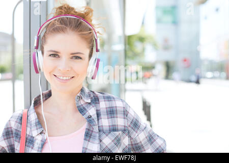 Portrait of happy woman wearing headphones lors de l'attente à l'arrêt de bus Banque D'Images