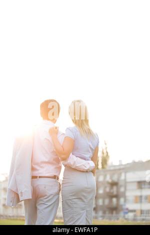 Vue arrière du business couple debout, les bras autour de contre ciel clair aux beaux jours