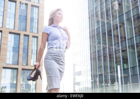Low angle view of confident businesswoman holding High heels, les édifices à bureaux Banque D'Images