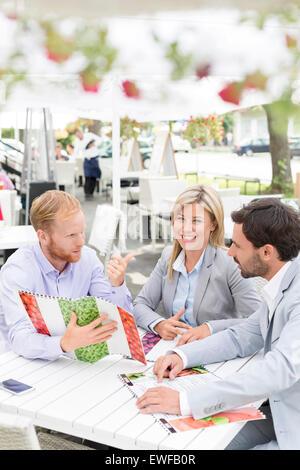 Portrait of happy businesswoman avec collègues masculins menu décider at sidewalk cafe Banque D'Images