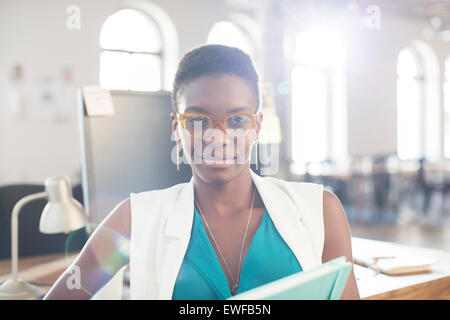 Portrait of confident businesswoman wearing eyeglasses in office Banque D'Images