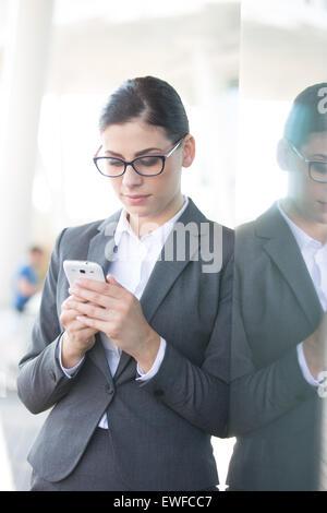 Businesswoman using cell phone tout en s'appuyant sur la paroi de verre Banque D'Images