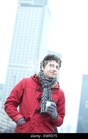 L'homme réfléchi en vêtements chauds holding disposable cup à l'extérieur Banque D'Images