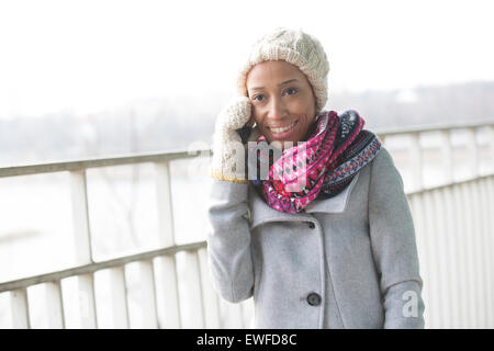 Happy woman in winter wear using cell phone outdoors Banque D'Images