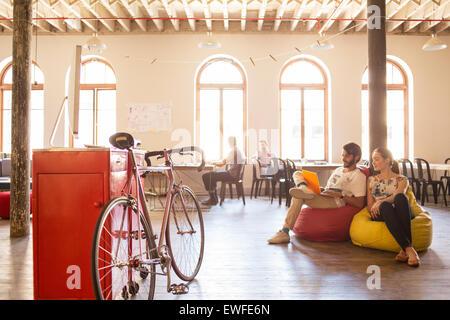 Creative business people using laptop sur des sièges-sacs in office Banque D'Images