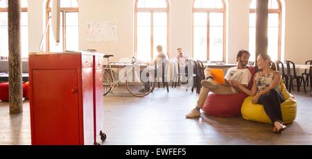Business people working at laptop sur chaises de sac d'haricot dans open office Banque D'Images