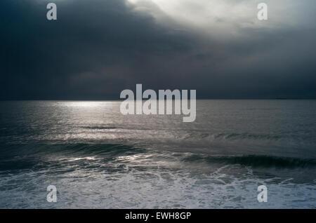 Ciel noir en hiver avec la lune reflétait sur l'océan Atlantique Nord comme une grosse houle de tempête et d'approches. Banque D'Images
