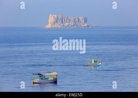 Les pêcheurs dans les bateaux de pêche traditionnelle maltaise la pêche au large de l'île de Fifla, Malte Banque D'Images