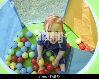 Petit garçon plaing dans une piscine à balles à l'extérieur Banque D'Images
