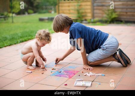 Frère et sa petite sœur à jouer ensemble dans la cour de la peinture avec de la craie de couleur Banque D'Images