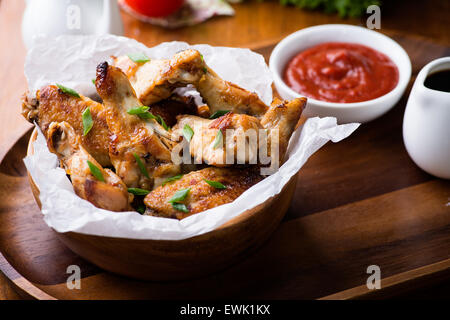 Ailes de poulet frit avec des sauces à bol en bois, selective focus Banque D'Images